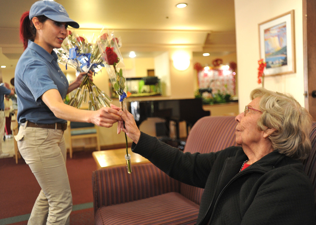 Description of . Tamara Torres, with Honda, Gives resident, Isabel Fruta, a receive long-stem red rose on Valentine's Day at Merill Gardens in Whittier on Thursday February 14, 2013.  The Helpful Guys in Blue, a group sponsored by the Southern California Honda Dealers Association surprise Whittier residents with a complimentary red roses. (SGVN/Staff Photo by Keith Durflinger)