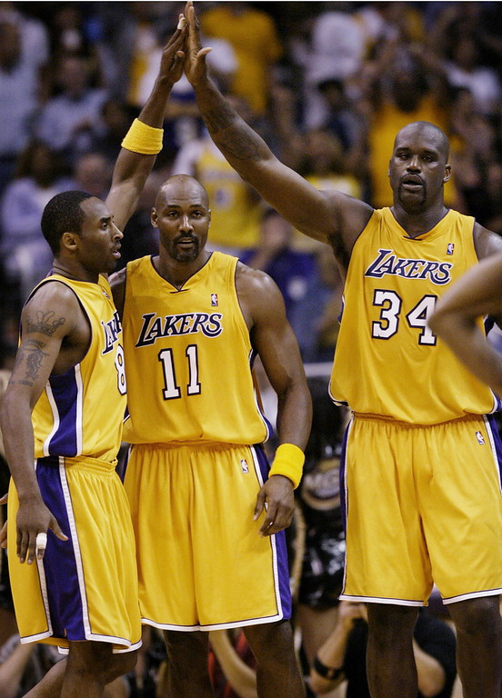 . The Los Angeles Lakers\' Kobe Bryant, left, is congratulated by teammates Shaquille O\'Neal, right, and Karl Malone after scoring against the Minnesota Timberwolves in the fourth quarter of Game 4 of the Western Conference Finals in Los Angeles, Thursday, May 27, 2004. (AP Photo/Kevork Djansezian)