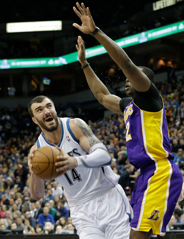 . Minnesota Timberwolves\' Nikola Pekovic of Montenegro, left, looks to shoot over Los Angeles Lakers\' Dwight Howard in the first quarter of an NBA basketball game Wednesday, March 27, 2013 in Minneapolis. (AP Photo/Jim Mone)