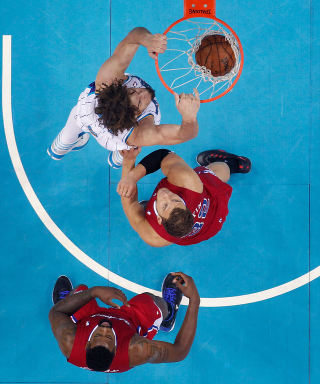 . New Orleans Hornets power forward Lou Amundson slam dunks in front of Los Angeles Clippers power forward Blake Griffin (32) and center DeAndre Jordan, bottom, in the first half of an NBA basketball game in New Orleans, Wednesday, March 27, 2013. The Clippers won 105-91. (AP Photo/Gerald Herbert)