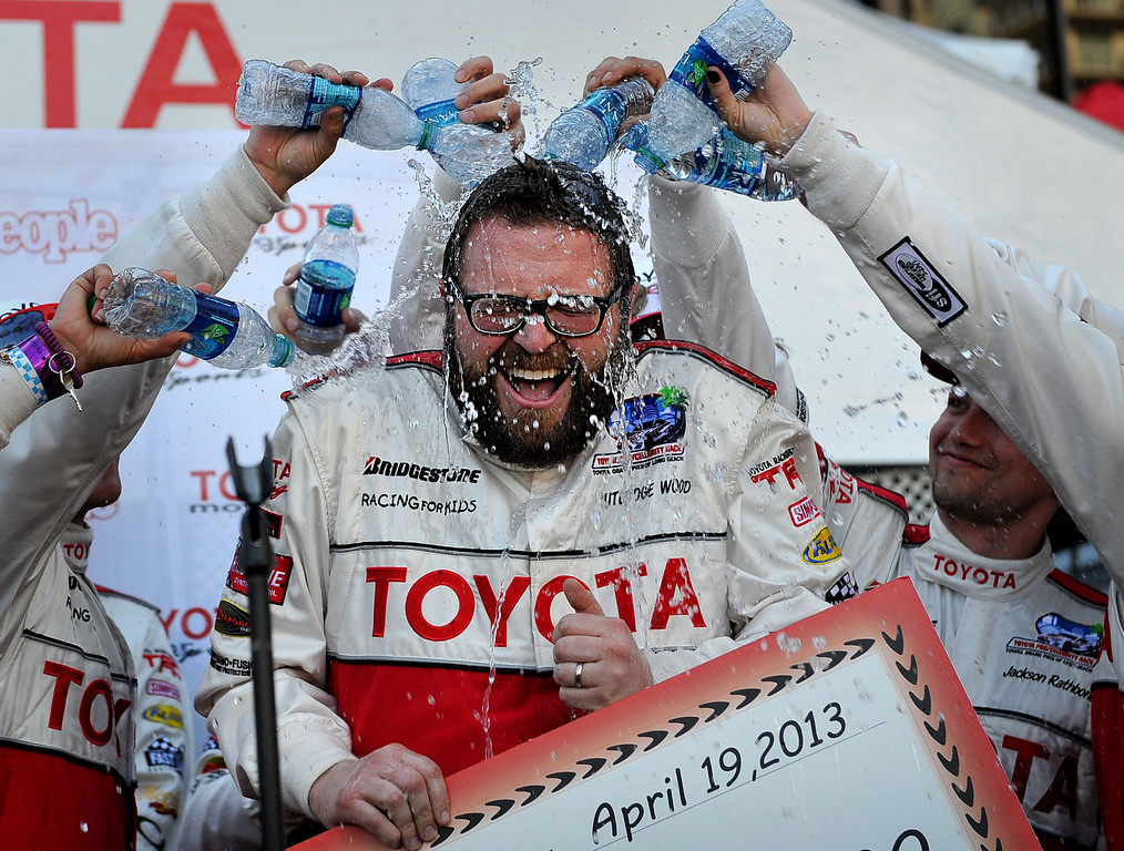 . 4/19/13 - Rutledge Wood is drenched with water from his fellow drivers after he won the pole position in the qualifying round of the Toyota Pro/Celebrity race at the 39th Annual Toyota Grand Prix of Long Beach. Wood received $15,000 from People magazine for his charity, Victory Junction. Photo by Brittany Murray / Staff Photographer
