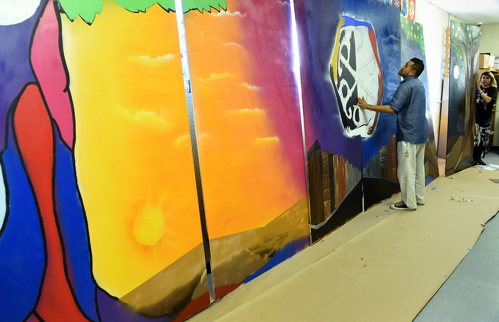 Description of . Special Programs Director Andrew Quinones arranges the mural at the San Gabriel Valley Conservation Corps YouthBuild Charter School in Pomona, CA, Wednesday, August 13, 2014. (Photo by Jennifer Cappuccio Maher/Inland Valley Daily Bulletin)