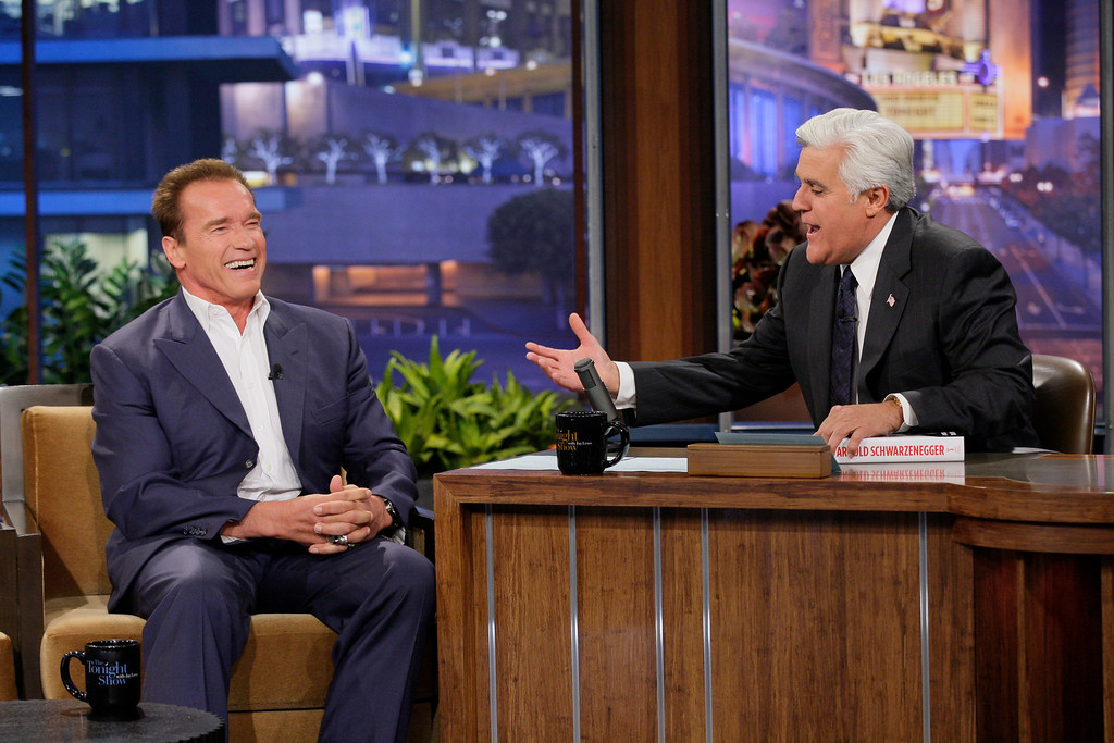 ". This Oct. 8, 2012 photo released by NBC shows former California Gov. Arnold Schwarzenegger, left, is interviewed by host Jay Leno on ""The Tonight Show with Jay Leno\"" in Burbank, Calif. NBC has cut the salary of the popular late night talk show host in an an effort by new owner Comcast Corp., to reboot the network.  (AP Photo/NBC, Paul Drinkwater)"