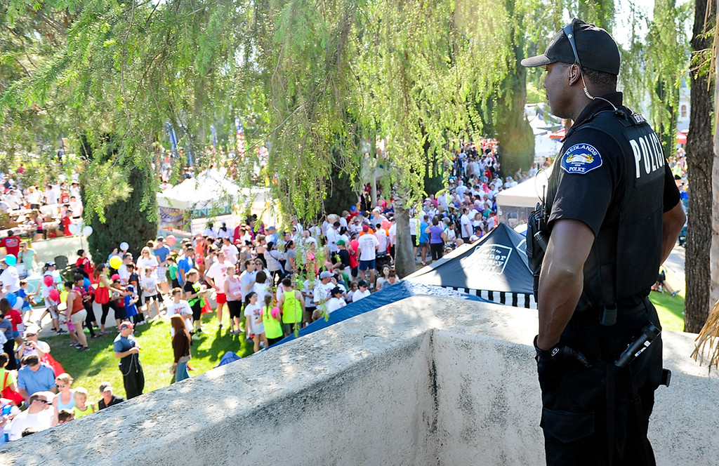 Description of . A Redlands police officer stands on the roof of the Redlands Bowl as he keeps watch around the finish line area of the 30th annual Run Through Redlands race on Sunday, April 21, 2013. The race proceeds benefited the Kiwanis Club Foundation and scholarship opportunities for high school seniors. (Rachel Luna / Staff Photographer)
