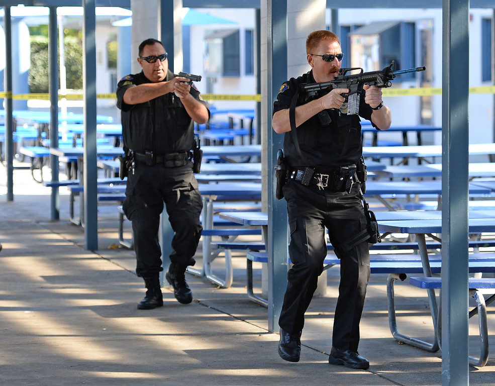 . The Hermosa Beach and Manhattan Beach Police Depts. conducted an active shooter drill on the campus of Hermosa Valley School Monday, November 25, 2013, Hermosa Beach, CA.   Officers responded to staged calls of a gun man on the campus, had to find and neutralize the suspect. Students also participated in the drill to give it more realism.  Officers stream onto campus into the direction of the shooting. Photo by Steve McCrank/DailyBreeze