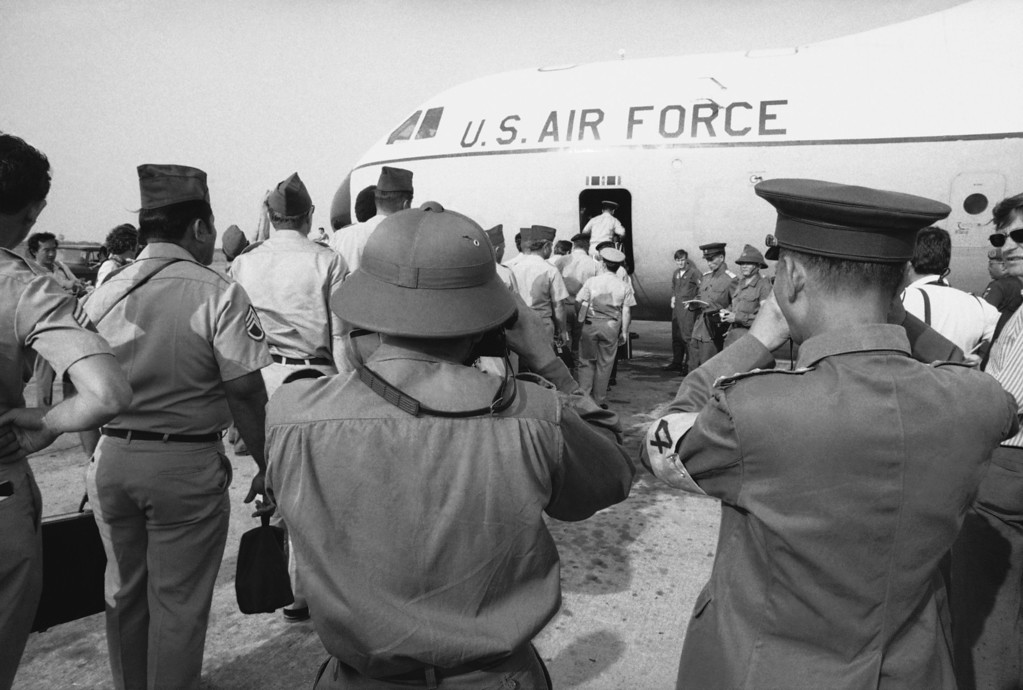 Description of . Viet Cong and North Vietnamese members of the joint military commission (foreground) snap pictures of U.S. troops as they board an Air Force plane for the flight home from Saigon's Tan Son Nhut Air Base, March 27, 1973. Withdrawal of these and other U.S. military personnel resumed after it was delayed to insure release of American POWs captured in Laos. (AP Photo/Neal Ulevich)