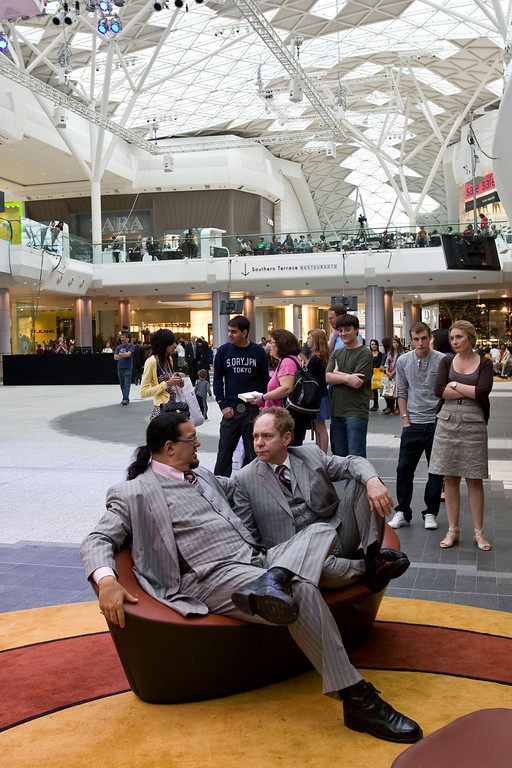 . U.S. illusionists and magicians Penn Jillette, left, and Raymond Teller talk to each other as they wait for a tv interview before their performance at Westfield Shopping centre in London to promote their 5 night Penn & Teller shows, starting Wednesday, in London, Tuesday, July 13, 2010. (AP Photo/Sang Tan)