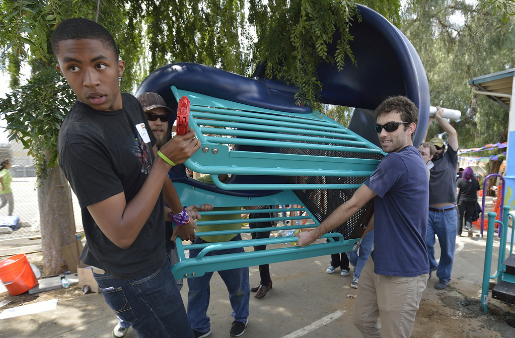 . LONG BEACH, CALIF. USA -- Volunteers carry a big slide during a one-day playground build at Edison Elementary School in Long Beach, Calif., on April 6, 2013.  More than 200 volunteers from the Long Beach Unified School District, Green Long Beach! and Zynga, joined organizers from KaBOOM! and residents to build a new playground at the Edison Child Development Center.  The playground is the fourth built by KaBOOM! and Zynga.org and is one of more than 150 playground builds KaBOOM! will lead across the country in 2013 in an effort to fulfill its vision of a great place to play within walking distance of every child in America. Photo by Jeff Gritchen / Los Angeles Newspaper Group