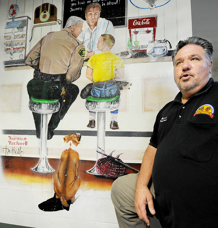 Description of . Rick Belmonte of Belmonte's Dog Training and Equipment discussing the copy of a Norman Rockwell mural on the wall that was painted by inmates which added a dog,