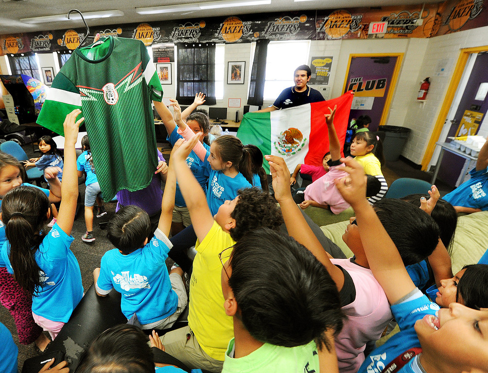 . Sonia Thong, Program Director holding up a Mexico team jersey, asking the kids who wants to wear it during the game. Kids enjoy watching the World Cup soccer game between Brazil and Mexico at Boys & Girls Club of East Los Angeles at 324 MCDonnell Avenue in Los Angeles, that ended in a 0-0 tie Tuesday, June 17, 2014.(Photo by Walt Mancini/Pasadena Star-News)