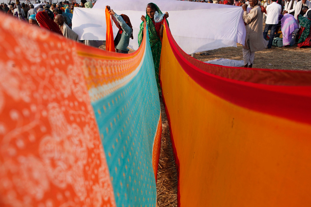 . Indian Hindu devotees dry their cloths after a holy dip at Sangam, the confluence of the Rivers Ganges, Yamuna and mythical Saraswati, during Maha Kumbh festival, in Allahabad, India,Thursday, Feb. 14, 2013. Millions of Hindu pilgrims are attending the Maha Kumbh festival, which is one of the world\'s largest religious gatherings that lasts 55 days and falls every 12 years. During the festival pilgrims bathe in the holy Ganges River in a ritual they believe can wash away their sins. (AP Photo/ Rajesh Kumar Singh)