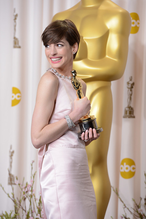 Description of . Anne Hathaway accepts the award for best actress in a supporting role for