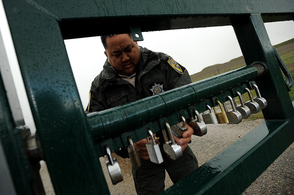 . California Department of Fish and Wildlife Warden Kyle Chang unlocks an entry gate at the San Jacinto Wildlife Area in Hemet March 8, 2013.  GABRIEL LUIS ACOSTA/STAFF PHOTOGRAPHER.