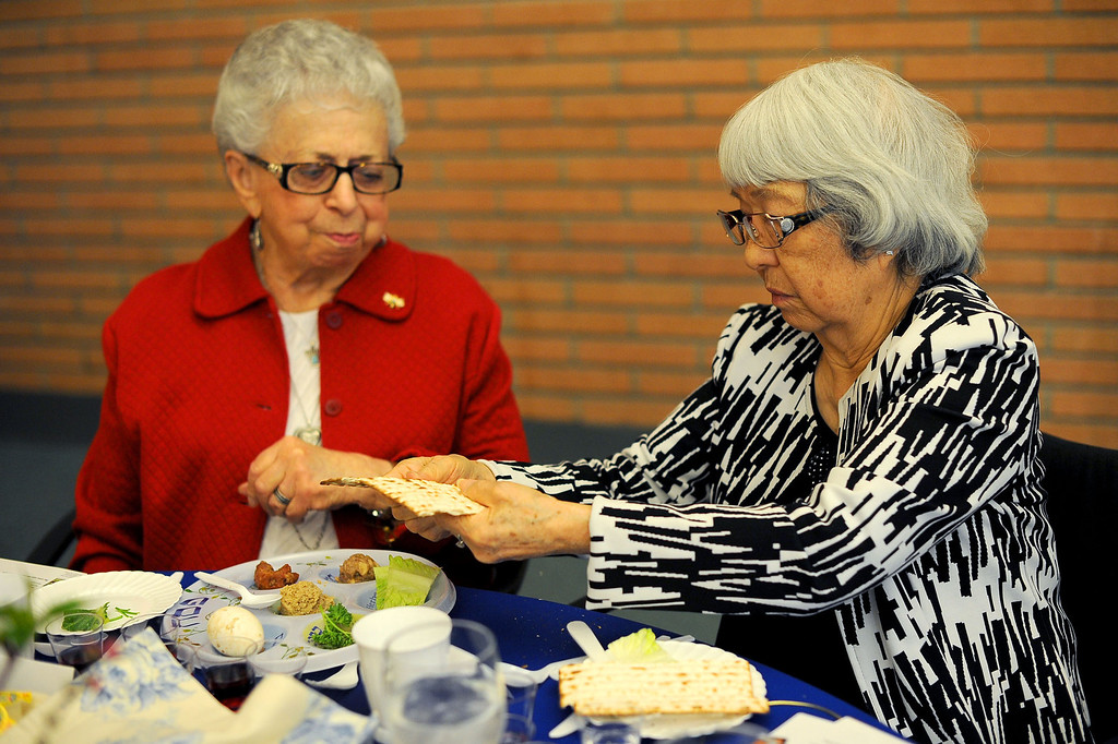 . Yuri Murayama and Miriam Gurwitz share matzah during a traditional Passover Seder at the Los Angeles Jewish Home in Reseda, CA March 20, 2013.  More than a dozen residents of Keiro Senior Healthcare in Boyle Heights joined residents of the Los Angeles Jewish Home for the religious celebration Wednesday.(Andy Holzman/Los Angeles Daily News)
