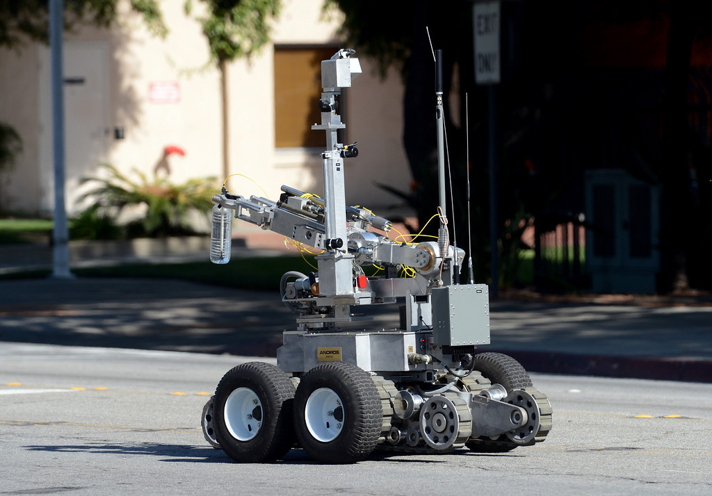Description of . 0419_NWS_IDB_L-POMONA-02-JCM (Jennifer Cappuccio Maher/Staff Photographer) An LA County Sheriff's Bomb Squad robot rolls toward a suspicious package as officials prepare to detonate it Thursday, April 18, 2013, at the corner of W Mission Blvd and S Main Street in Pomona.