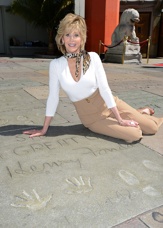 . Jane Fonda poses in front of her father, Henry Fonda\'s hand and footprint as the 2013 TCM Classic Film Festival honors Jane Fonda with a handprint and footprint ceremony at the TCL Chinese Theatre on Saturday, April 27, 2013 in Los Angeles. (Photo by Jordan Strauss/Invision/AP)