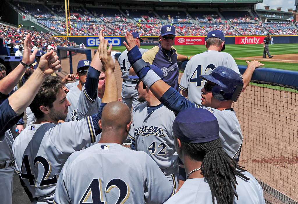 Description of . ATLANTA - APRIL 15: Aramis Ramirez of the Milwaukee Brewers is congratulated by teammates after scoring a second inning run against the Atlanta Braves at Turner Field on April 15, 2012 in Atlanta, Georgia.  All uniformed team members are wearing jersey number 42 in honor of Jackie Robinson Day. (Photo by Scott Cunningham/Getty Images)