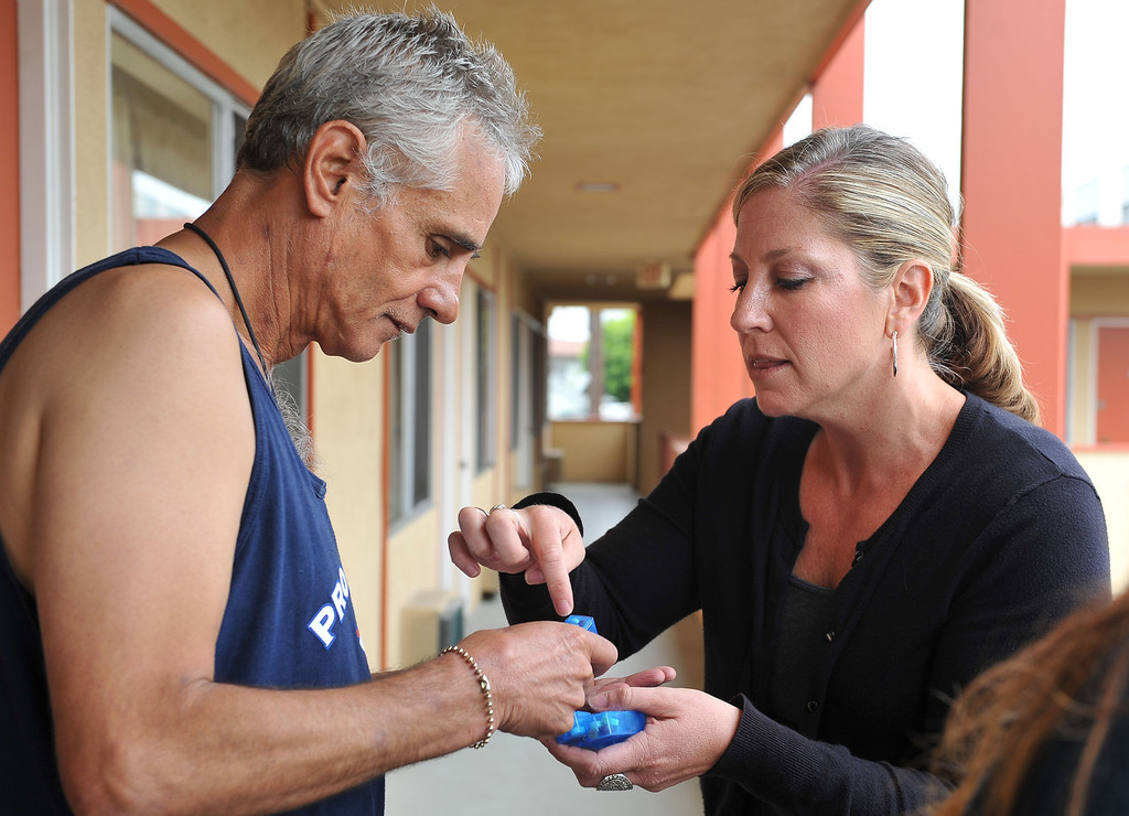 . 080913 - L-R Felipe Rodriguez gets his medication from Lesley Braden, a registered nurse from Homeless Innovations Project of Mental Health America. Rodriguez has been a client since November 2012 after 7 years of being homeless. Braden administers his medication every 3 days to prevent mis-use or abuse. Photo by Brittany Murray, Press Telegram