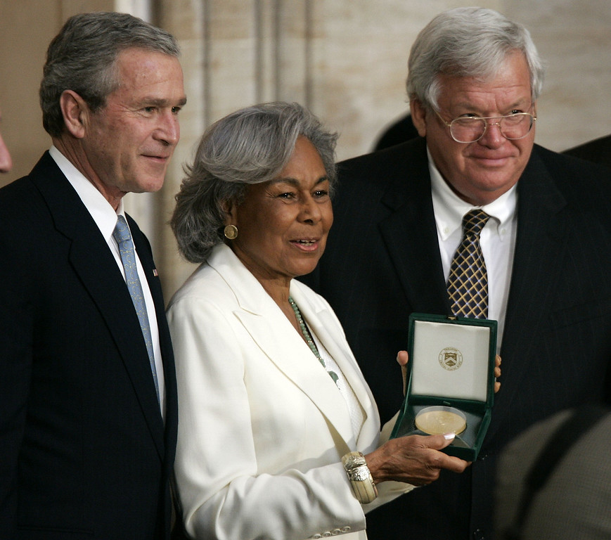 Description of . WASHINGTON - MARCH 2:  Flanked by U.S. President George W. Bush (L) and Speaker of the House Dennis Haster (R-IL) (R), Rachel Robinson (C), widow of baseball player Jackie Robinson receives the Congressional Gold Medal that is presented to her husband during a ceremony March 2, 2005 on Capitol Hill in Washington, DC. Jackie Robinson was recognized for his legendary baseball career, his lifetime of breaking down barriers and his unending fight for justice.  (Photo by Alex Wong/Getty Images)