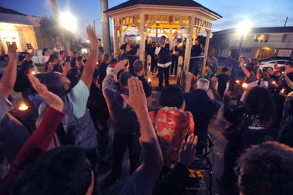 . Pastor Jim Ortiz leads prayer as residents gather for a community-wide prayer vigil at Central Park in Whittier in response to recent attempted child abductions on Friday March 15, 2013. About 150 people attended the candlelight vigil led by Pastor Sam Gamboa of the Good Shepherd Family Bible Church and organized by the Whittier Area Evangelical Ministerial Alliance. City and police officials joined citizens and area church members as they prayed for protection of the children and the arrest of the suspects. (SGVN/Staff Photo by Keith Durflinger)