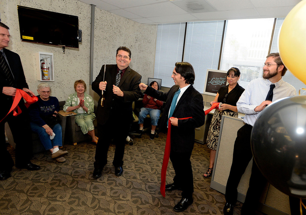 Description of . LANG Vice President and CEO Michael Anastasi, left, and Sun Metro Editor Ryan Carter, right, perform a ribbon cutting ceremony during The Sun's Open House in downtown San Bernardino March 13, 2013.  GABRIEL LUIS ACOSTA/STAFF PHOTOGRAPHER.