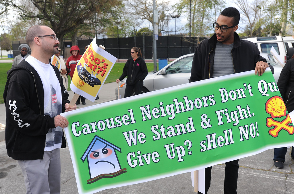 . Residents of the Carousel Tract neighborhood in Carson staged a protest against Shell Oil Friday by marching with signs from Dolphin Park to a Shell facility on Wilmington Avenue.  John Harrison and Donovan Brown unfurl their protest sign. 20130308 Photo by Steve McCrank / Staff Photographer