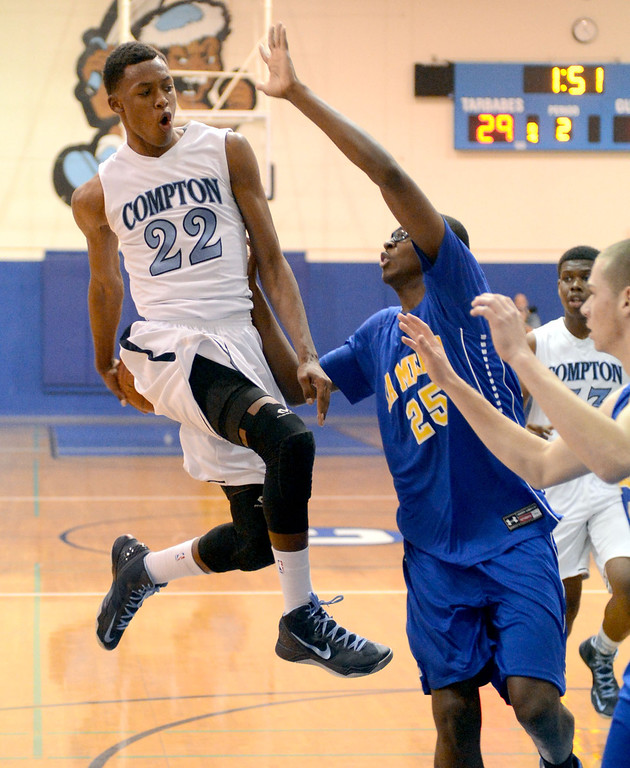 Description of . Compton's Isaiah Bailey (22) makes a pass behind his back, faking the shot, behind La Mirada's Dezmon Murphy (25) in a first round CIF Division 3AAA basketball game Wednesday night in Compton. 20130213 Photo by Steve McCrank / Staff Photographer
