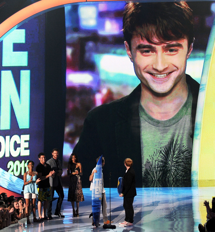 . UNIVERSAL CITY, CA - AUGUST 07:  Actors Tom Felton (L) and Rupert Grint with Daniel Radcliffe via satellite accept the Harry Potter awards onstage during the 2011 Teen Choice Awards held at the Gibson Amphitheatre on August 7, 2011 in Universal City, California.  (Photo by Kevin Winter/Getty Images)