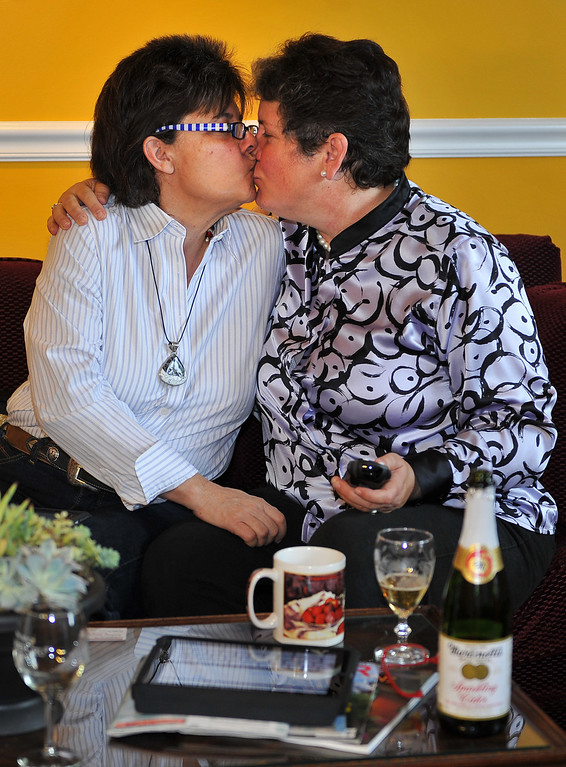 . 6/26/13 - L-R Stephanie Loftin and Reba Birmingham, a married lesbian couple since 2008, and attorneys in Long Beach, watch the SCOTUS decisions on DOMA and Prop 8 in their home on Wednesday morning. They felt it was a good day for California but there is still more work to be done. Photo by Brittany Murray / Staff Photographer