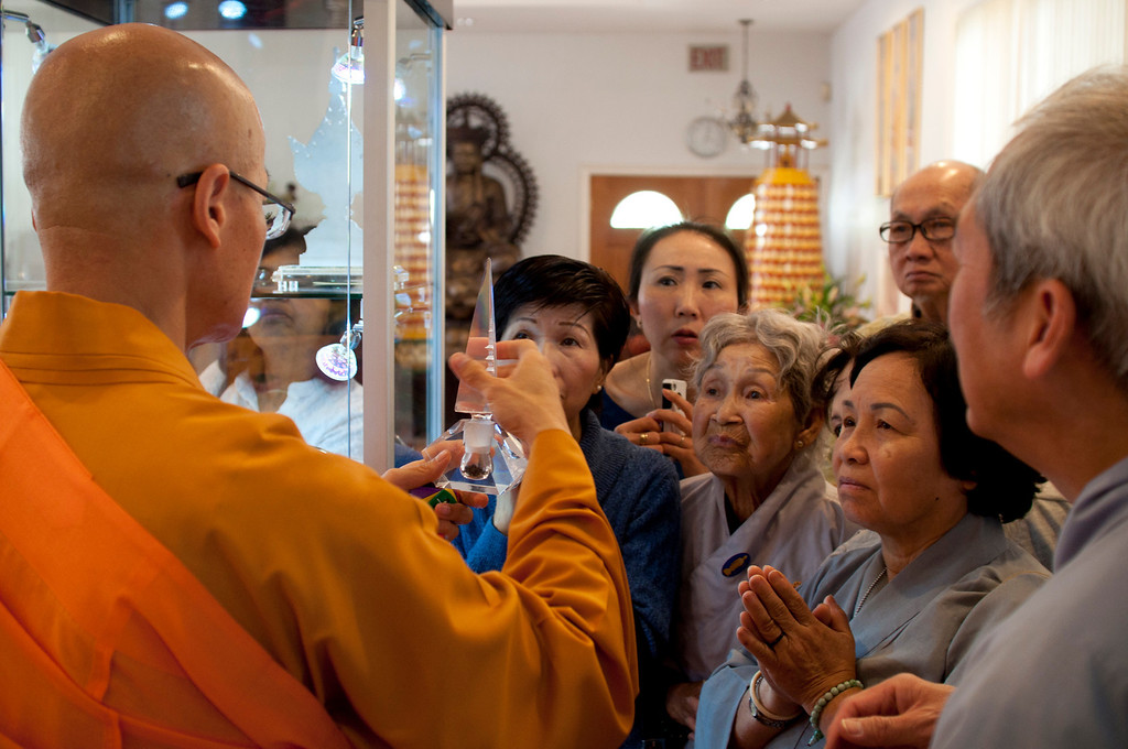 Description of . Dharma Master YongHua shows a crowd hair shariras on display at Lu Mountain Temple in Rosemead, Calif., Sunday, March 31, 2013. Several shariras were made available for viewing to the public including a rare Shakyamuni Buddha tooth relic measuring about two inches in height. (SGVN/Correspondent photo by Anibal Ortiz)