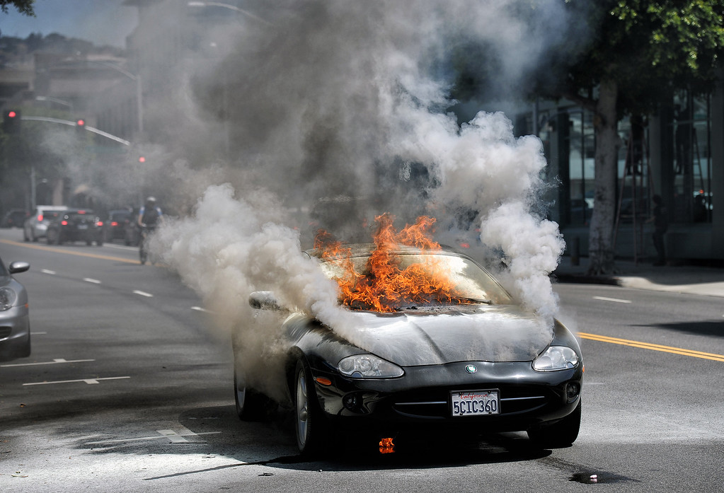. A car burns  in front of 141 S Robertson Blvd, Beverly Hills, CA Tuesday, July 16, 2013. The female driver was able to exit the vehicle and was unhurt. (Hans Gutknecht/Los Angeles Daily News)