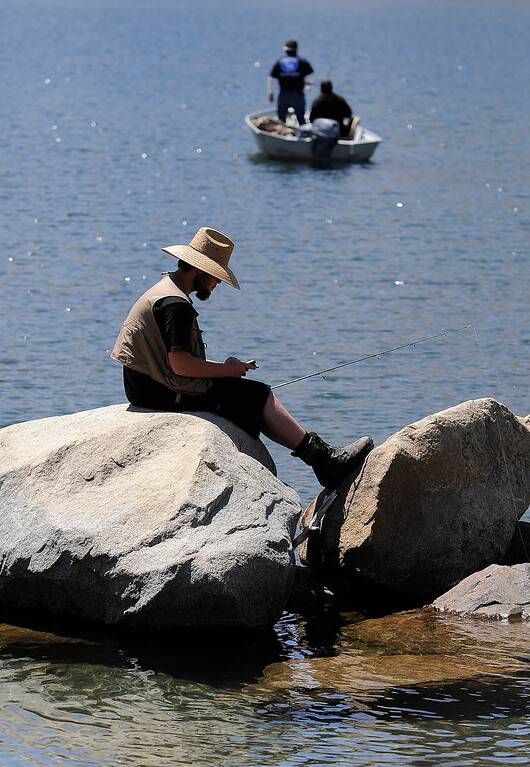 . A fisherman appears to be catching up on his email, or maybe he is sending a text on opening day of Trout Fishing Season in the Eastern Sierra. Convict Lake, CA 4/27/2013(John McCoy/Staff Photographer)