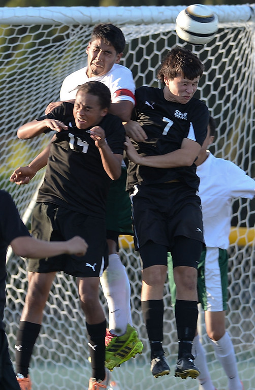 . Narbonne\'s Angel Hernandez (16) clears the ball away from San Pedro\'s Justin Norton (14) and Daniel Powell (7) in a Marine League boys soccer game Wednesday, February 12, 2014, Harbor City, CA.  Narbonne won 2-0 and seals the league title. Photo by Steve McCrank/Daily Breeze