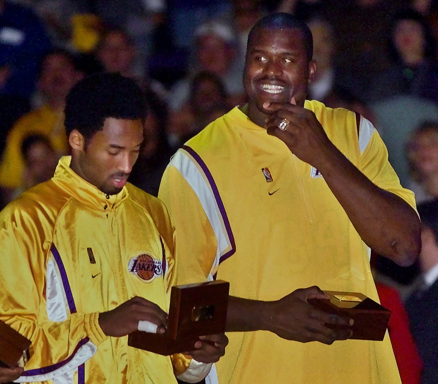 . Los Angeles Lakers\' Shaquille O\'Neal, right, shows off his championship ring as teammate Kobe Bryant looks at his ring during pre-game ceremonies in Los Angeles, Wednesday, Nov. 1, 2000. The world champion Lakers were scheduled to meet the Utah Jazz in their home. (AP Photo/Kevork Djansezian)