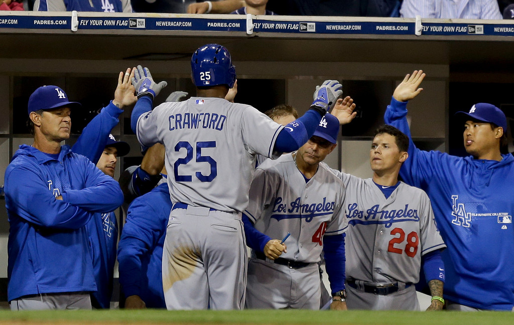 . Los Angeles Dodgers\' Carl Crawford is congratulated at the dugout after scoring from third on a hit by Mark Ellis during  the fifth inning of a baseball game against the San Diego Padres in San Diego, Wednesday, April 10, 2013. (AP Photo/Lenny Ignelzi)