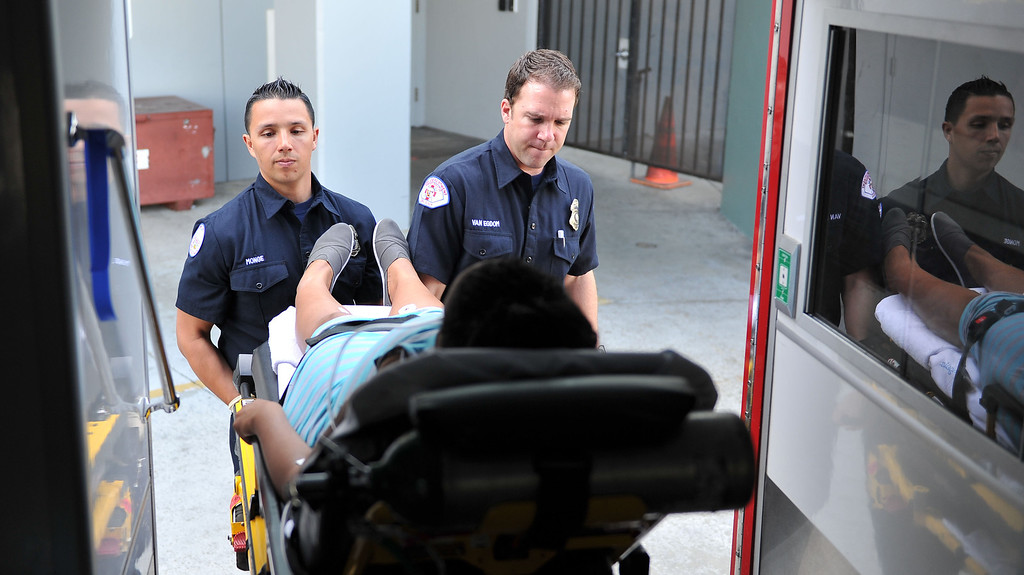 . 2/15/13 - L-R Paramedics Luis Monge and Matt Van Egdon right tend to a pregnant patient in possible early labor. Currently each rescue truck for the Long Beach Fire Department is manned by two paramedics. The city  proposed staffing change would place one paramedic and one EMT in the truck. Legally EMT\'s are limited in the care they can provide, therefore in case of a critical patient the one paramedic responding would be responsible for multiple tasks. Photo by Brittany Murray / Staff Photographer