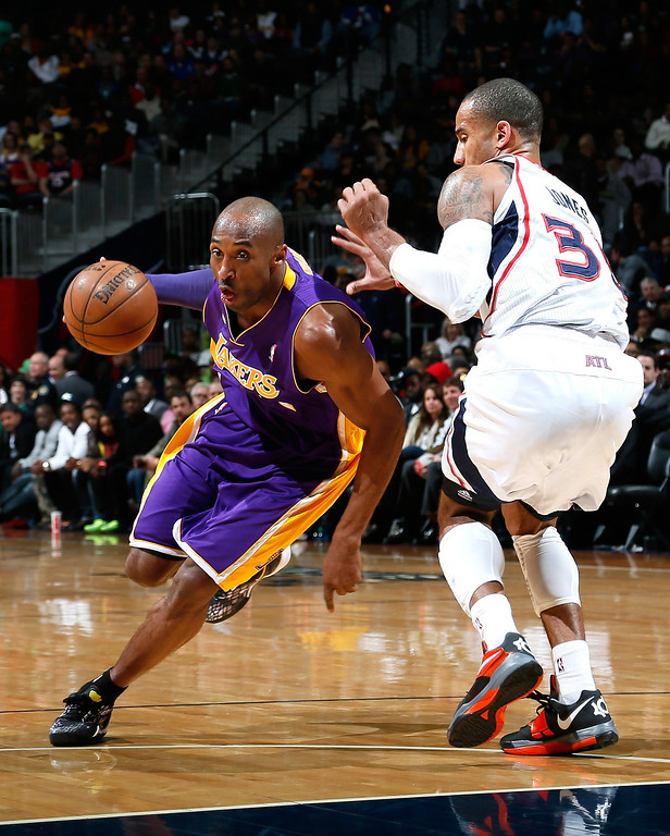 . ATLANTA, GA - MARCH 13:  Kobe Bryant #24 of the Los Angeles Lakers drives around Dahntay Jones #30 of the Atlanta Hawks at Philips Arena on March 13, 2013 in Atlanta, Georgia.  NOTE TO USER: User expressly acknowledges and agrees that, by downloading and or using this photograph, User is consenting to the terms and conditions of the Getty Images License Agreement.  (Photo by Kevin C. Cox/Getty Images)