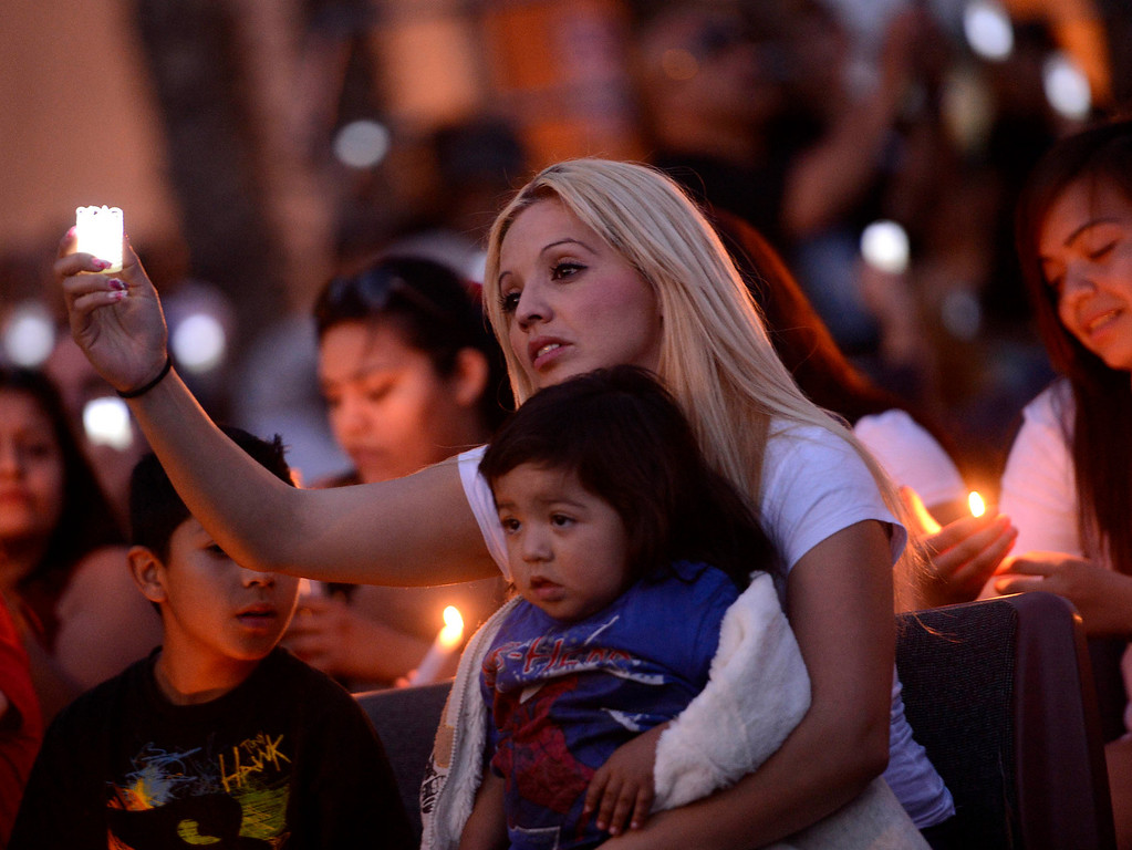 Description of . Alma Espinoza with son Isaac, 1, commemorate the life of her nephew Robert Elizarraraz during the annual Victims Candlelight Vigil at the police station in San Bernardino April 23, 2013.    Elizarraraz died February of 2012 as a victim of violence.  GABRIEL LUIS ACOSTA/STAFF PHOTOGRAPHER.