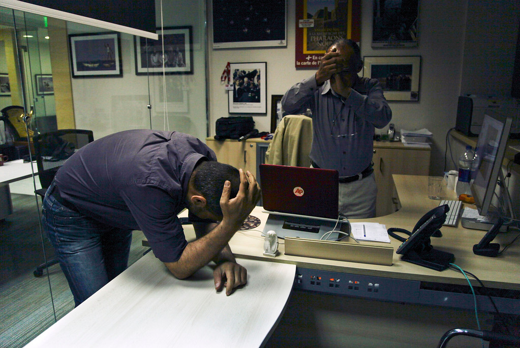 . Associated Press photographer Khalil Hamra reacts after hearing that his photographs were part of an Associated Press team entry that won the Pulitzer prize for their photographs from Syria, in Cairo, Egypt, Monday, April 15, 2013. The Pulitzer in breaking news photography went to The Associated Press for its coverage of the civil war in Syria. Middle East Regional photo editor Manoocher Deghati applauds at right. (AP Photo/Nariman El-Mofty)