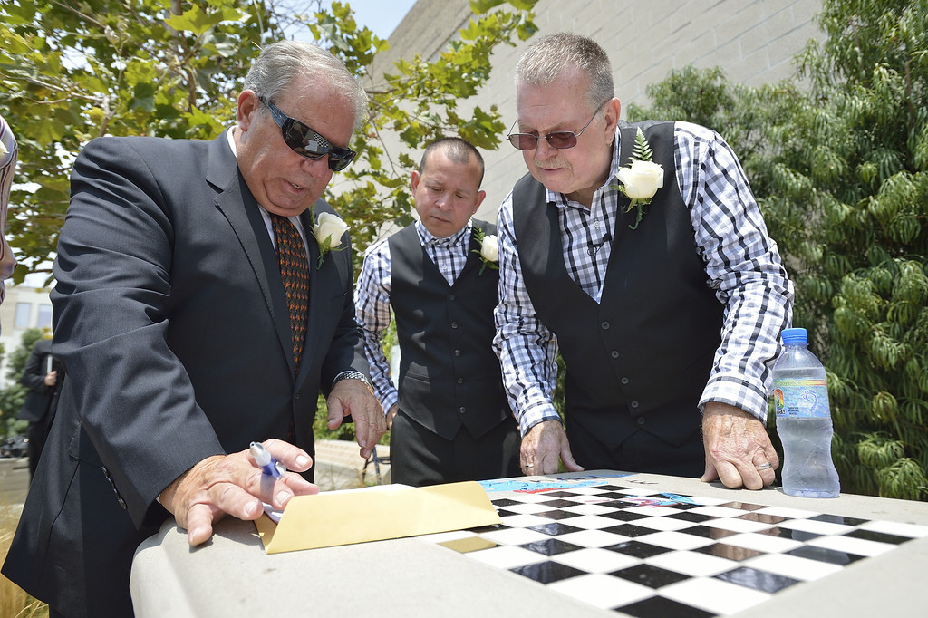 . LONG BEACH, CALIF. USA -- Long Beach residents Bob Crow, right, and Tony Almeida, go over paperwork with Long Beach Mayor Bob Foster after getting married at Harvey Milk Plaza in Downtown Long Beach, Calif., on July 1, 2013. Long Beach Mayor Bob Foster performed the marriage ceremony for the couple. Crow, who founded Long Beach Pride, asked Foster to perform the ceremony years ago.  Photo by Jeff Gritchen / Los Angeles Newspaper Group