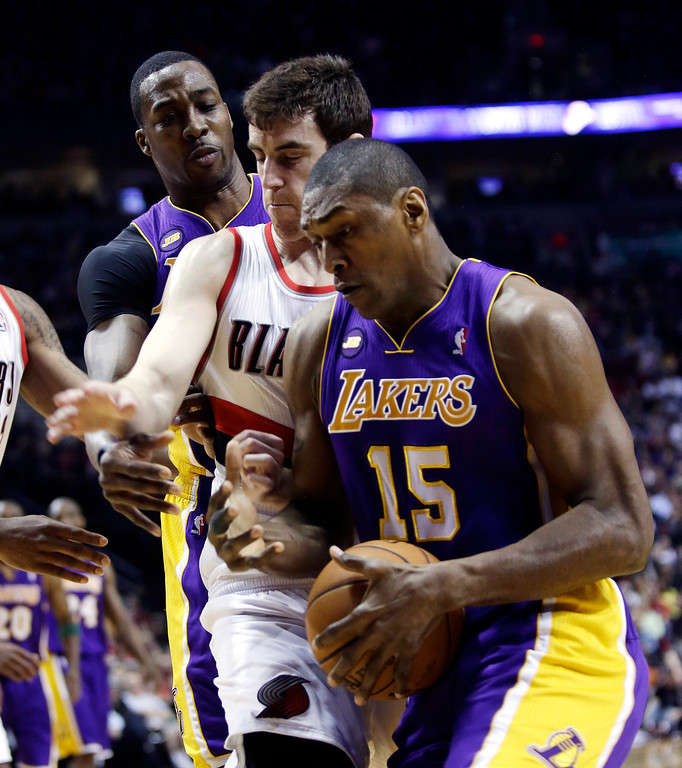 . Los Angeles Lakers center Dwight Howard, left, passes inside to forward Metta World Peace, right, past Portland Trail Blazers forward Victor Claver, from Spain, during the first quarter of an NBA basketball game in Portland, Ore., Wednesday, April 10, 2013.(AP Photo/Don Ryan)