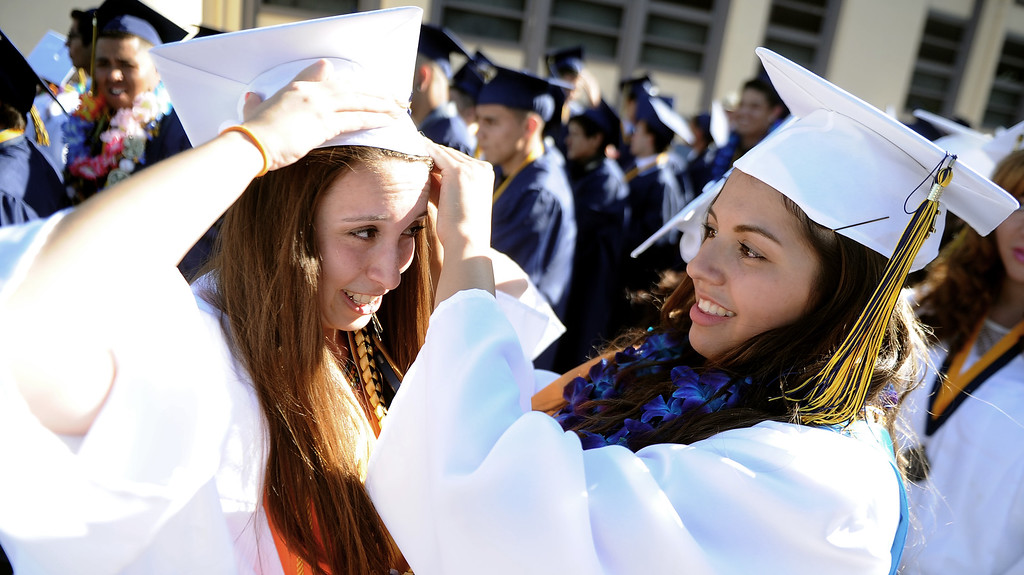 Description of . Students Fernanda Sanchez, left, with Monica Espinoza prepare prior to the Montebello High School commencement at Montebello High School on Thursday, June 20, 2013 in Montebello, Calif.  (Keith Birmingham/Pasadena Star-News)