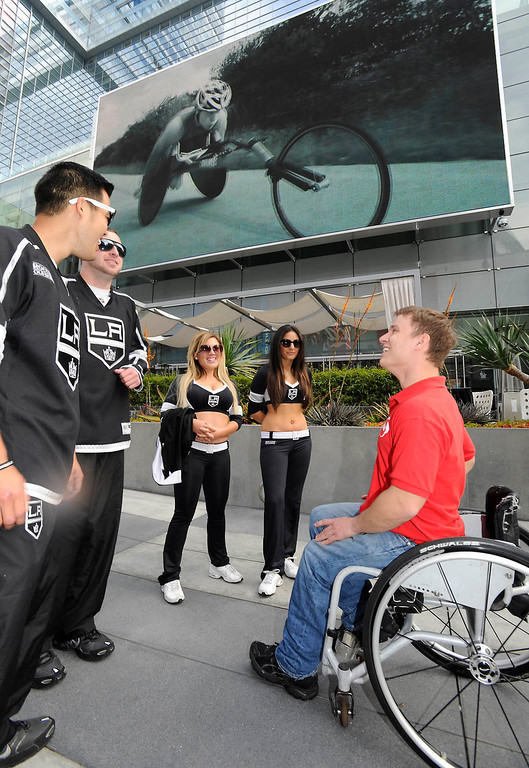 ". Ryan Chalmers talks to members of the LA Kings Ice Crew outside the JW Marriott at LA Live. Chalmers is pushing himself in a wheel chair on a coast-to-coast trip that starts at the JW Marriott in Los Angeles, and will end in New York\'s Central Park. The 3000 mile odysey will raise funds for an organization called  ""Stay Focused\"" that allows teens and young adults with disabilities to participate in sports alongsid able-bodied people.  Los Angeles CA 4/6/2013(John McCoy/Staff Photographer"