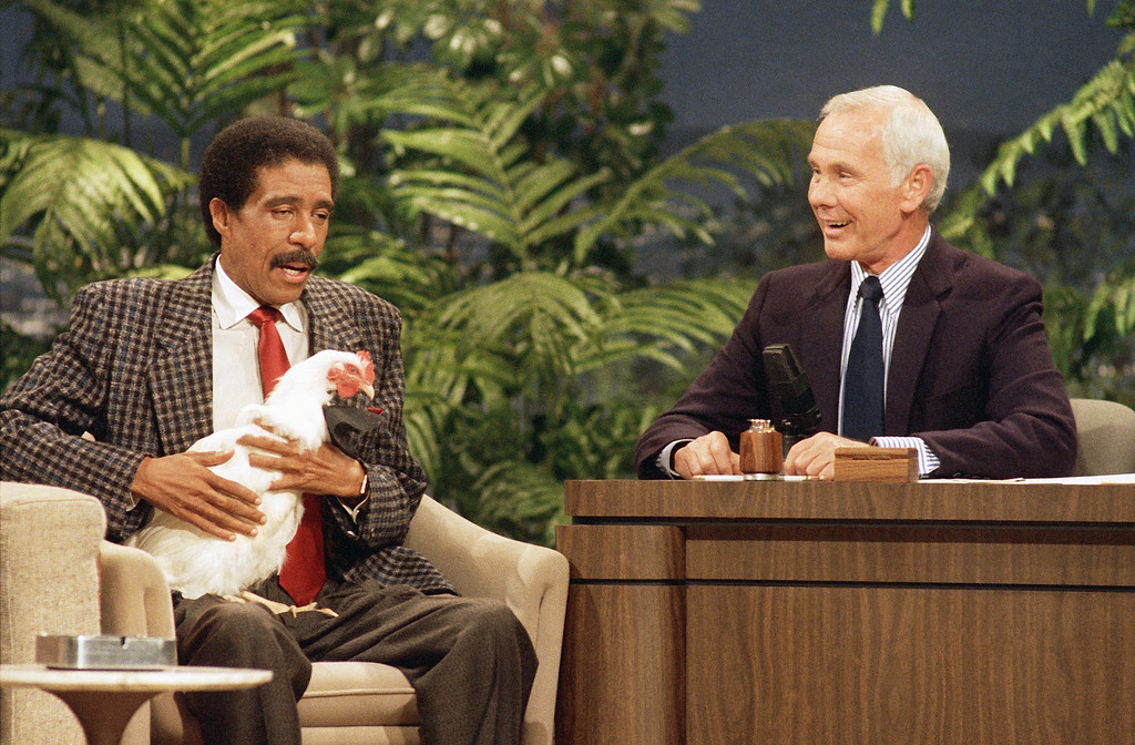 """. Richard Pryor holds a chicken while speaking with Johnny Carson on \""""The Tonight Show\"""" at the NBC studio in Burbank, Calif., Oct. 9, 1986.  (AP Photo/Tweed)"""