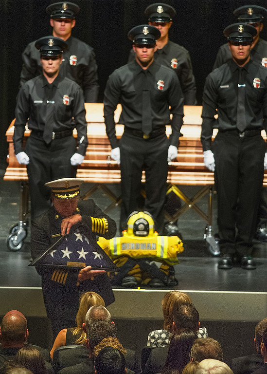 Description of . Arcadia Fire Chief Kirt Norwood presents the American Flag to Michael Herdman wife Brigitte Herdman at Michael Herdman  memorial service on Wednesday, July 9, 2014, for the Arcadia firefighter-paramedic found dead in the Los Padres National Forest last Friday. Herdman, an avid adventurer, died after becoming separated from his camping partner. He fell from a cliff and was killed by his injuries. Searchers canvassed the forest for 11 days before finding his body.(Photo by Walt Mancini/Pasadena Star-News)
