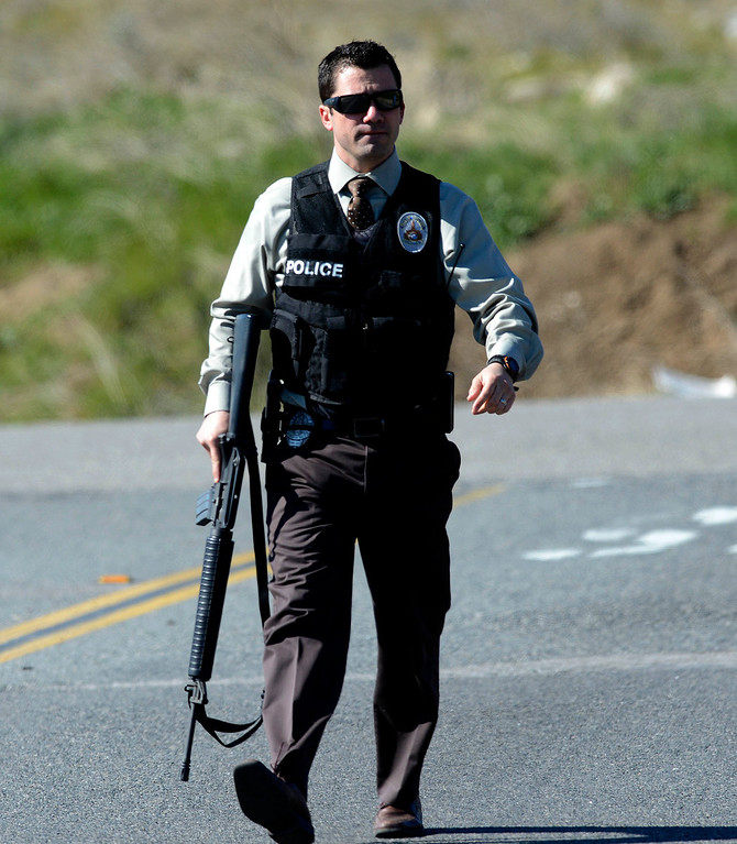 Description of . A Redlands Police officer executes a blockade at Highway 38 and Bryant Street near the Mill Street Ranger Station west of Yucaipa February 12, 2013.  Authorities believe that they exchanged gunfire with fugitive Christopher Dorner in the Barton Flats area of the San Bernardino National Forest.  Fish and Game officers spotted a man fitting the description of Dorner driving a white pick-up, and two San Bernardino County Sheriff Deputies exchanged gunfire with him.  GABRIEL LUIS ACOSTA/STAFF PHOTOGRAPHER.
