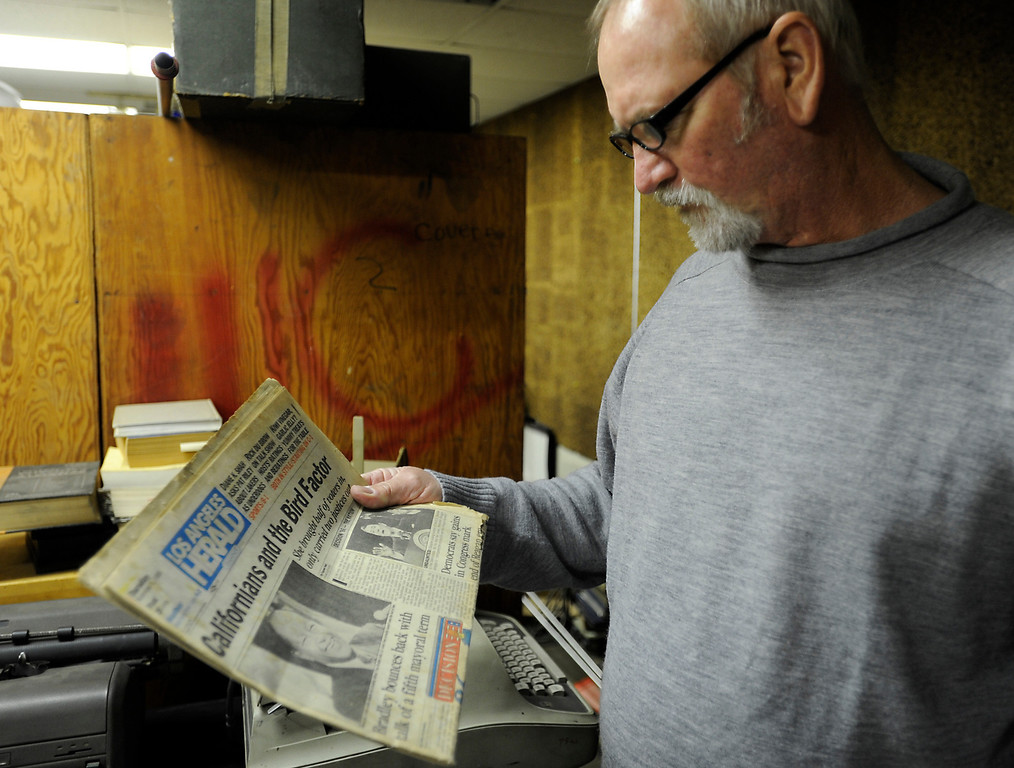 . Rob Brown looks at an old copy of the Herald Examiner that he picked up in the old darkroom that is now a storage area. Former photographers from the Los Angeles Herald Examiner gathered to day to take a tour of the old Herald Building, and then join for a panel discussion about their work and their days working at the old Herex. Los Angeles, CA 3/9/2013(John McCoy/Staff Photographer)