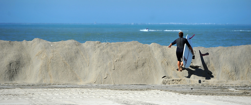 Description of . A surfer crosses the sand berm to gain access to waves inside the breakwall as high tide and a storm surge from Hurricane Marie had locals bracing for the worst in the Peninsula neighborhood in Long Beach, CA on Wednesday, August 27, 2014. With city crews constantly building a sand berm, the water was held back from the homes and streets during the morning high tide. (Photo by Scott Varley, Daily Breeze)