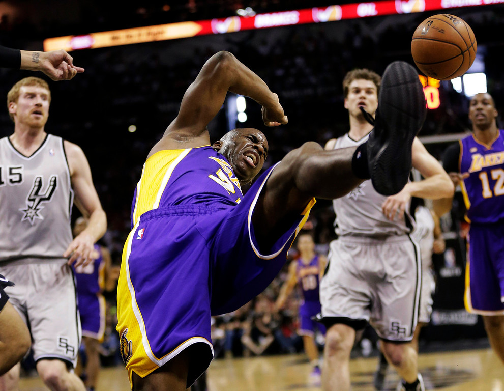 . Los Angeles Lakers\' Jodie Meeks, center, loses control of the ball as he drives to the basket against the San Antonio Spurs during the first half of Game 1 of their first-round NBA playoff basketball series, Sunday, April 21, 2013, in San Antonio. (AP Photo/Eric Gay)