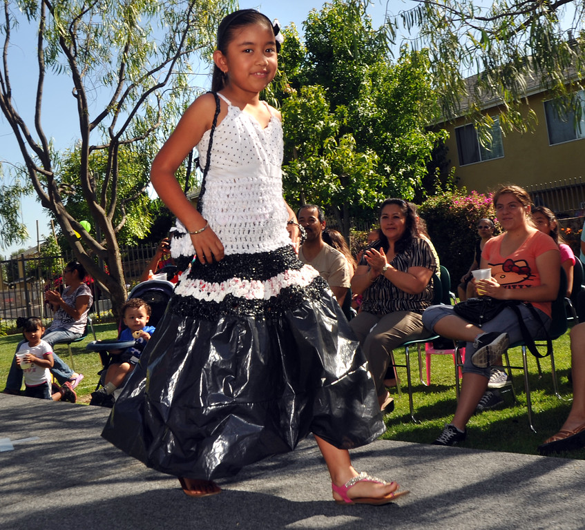 Description of . Melany Reynaga, 8, displays her plastic evening dress with a crocheted top and pleated plastic bag skirt in the